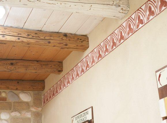 Decorazione realizzata con terre naturali su supporto di pittura a base di calce su parete di intonaco dilavato